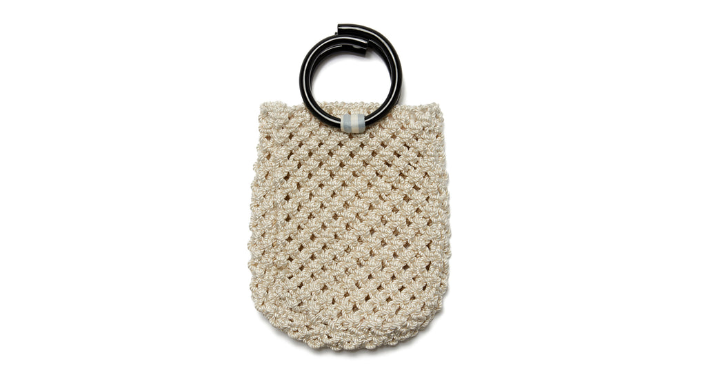 Full view of Mia Purse In Cream. We are so excited about our sophisticated take on the classic woven net bag. The Mia macrame purse in cream twist cord with black acrylic top handles is ready for city jaunts and beach strolls alike.