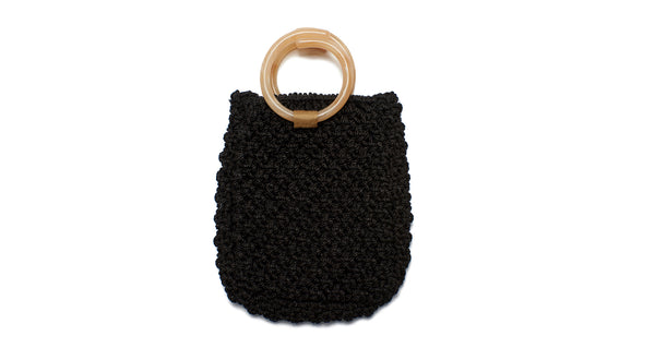 Full view of Mia Purse In Black. We are so excited about our sophisticated take on the classic woven net bag. The Mia macrame purse in black twist cord with tan acrylic top handles is ready for city jaunts and beach strolls alike.
