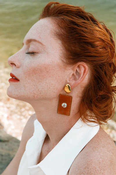 Thumbnail of model wearing the Santa Maria Earrings. Coming in hot! Get that warm weather glow with our gold-plated petal earrings, featuring bold peach aventurine rectangle drops set with faceted green amethyst stones.