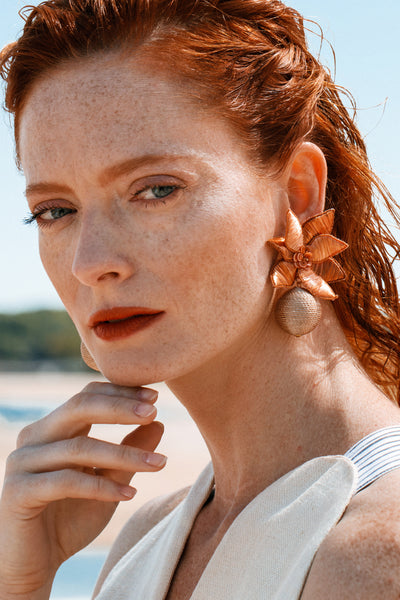 Thumbnail of model wearing the Tuscan Field Earrings. Molto Bene! Gild the lily this season in the prettiest pair of hand-embroidered and sequined amber flower earrings with tan thread wrapped drops.