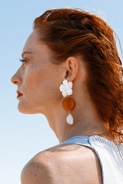 Thumbnail of model wearing the Paper White Drop Earrings In Amber. Bask in the ultra-flattering glow of our carved mother-of-pearl flower earrings, with warm amber-colored coil beads and lustrous freshwater baroque pearls.