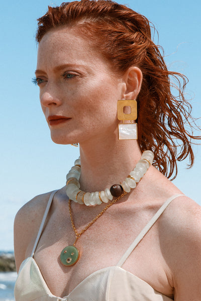 Thumbnail of model wearing the Geo Pearl Earrings. Fortune favors the bold. Square up your summer style in a pair of our gold-plated geometric and mother-of-pearl statement earrings.