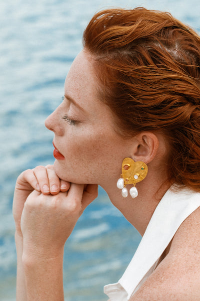 Thumbnail of model wearing the Divina Earrings. Whether you're beach-combing or strutting through the city, these gold-plated heart cutout earrings will garner a sea of compliments. Inset with peach moonstone, green onyx, mother-of-pearl, and pink tourmaline semiprecious stones and hanging freshwater pearls.
