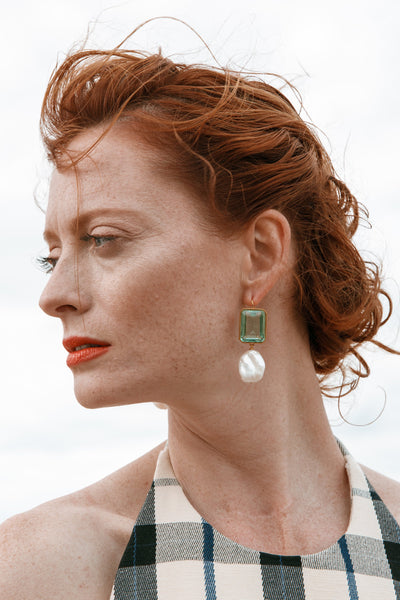 Thumbnail of model wearing the Aegean Earrings. Need some perfect little gems to tide you over til summer? Look no further than our radiant rectangle drop earrings, with aqua-colored quartz stones and hanging baroque freshwater pearls.