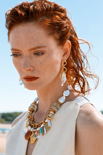 Thumbnail of model wearing the Pergola Earrings. You'll have it made in the shade (or the sun, of course) in our gold-plated multi-link earrings with hanging freshwater pearl and aqua-colored acrylic drops.