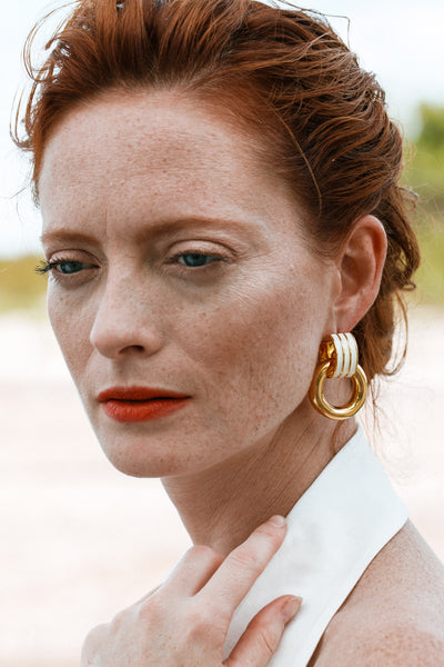 "Thumbnail of model wearing the Piazza Earrings In Cream. Knock knock, your chicest new accessory is here. We're confident these gold-plated ""door knocker"" earrings with hand-painted ivory enamel and hanging rings will be a timeless go-to pair."