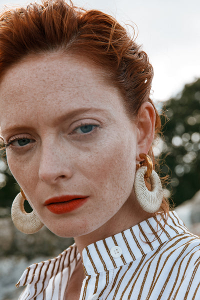 Thumbnail of model wearing the Orb Earrings. Make your hoop dreams come true in our gold-plated link earrings with metallic gold hand-woven thread pendants.