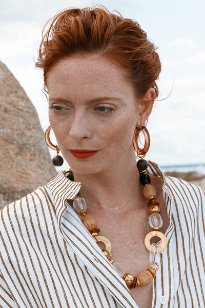 Thumbnail of model wearing the Spritz Hoops In Caramel. We love the ease and elegance of our large hoop earrings tinted in caramel-coloured acrylic, featuring hanging, removable wood bead drops. Great for daytime wear and for well after the sun's gone down.