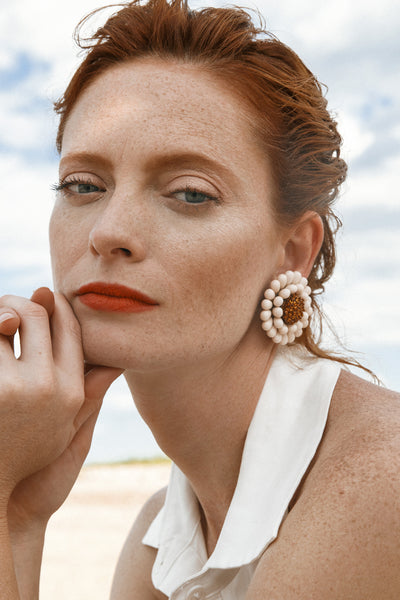 Thumbnail of model wearing the Sunflower Earrings. With their flattering shimmer and vintage vibes, these hand-beaded flower clip-ons are anything but your garden-variety earrings.