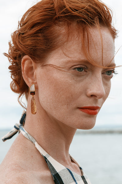 "Thumbnail of model wearing the Amber Drop Earrings. This season Lizzie took inspiration from the golden-hued sunsets of rustic Italy. Chase that warm light in our gold-plated earrings with mother-of-pearl ""fin"" tops, garnet, and carved citrine quartz drops."