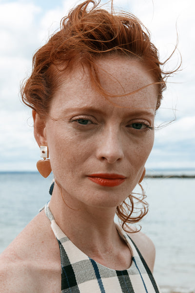 Thumbnail of model wearing the Venice II Earrings. We heart Venice! Show some love in the sweetest gold earrings, featuring mother-of-pearl rectangle tops set with faceted rhodolite and hanging peach aventurine heart drops.