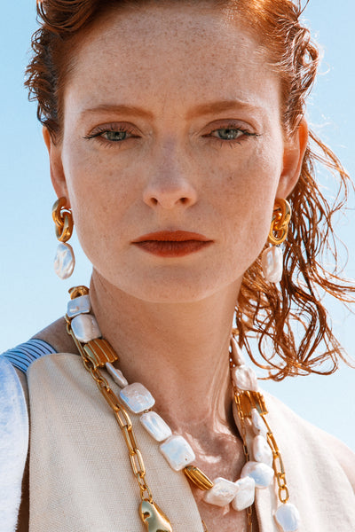 Thumbnail of model wearing the Perla Earrings. Trend-proof. Fail-safe. Meet your new sensual essential: a pair of gold-plated link earrings with hanging freshwater baroque pearls so perfect, you'll wear them for years to come.