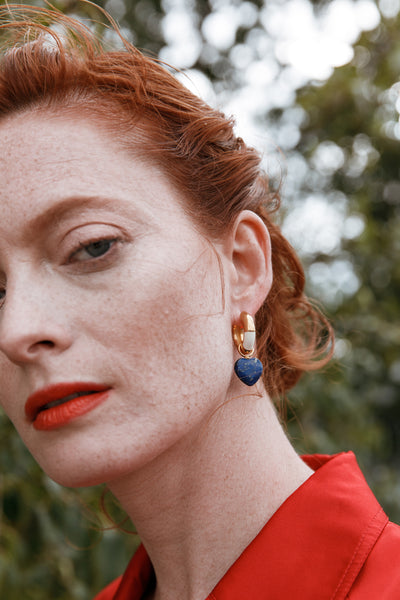 Thumbnail of model wearing the Life Saver Hoops In Cream. Inspired by the colorful striped buoys dotting the waters of Lake Como, our gold-plated mini hoop earrings will delight in hand-painted