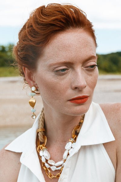 Thumbnail of model wearing the Blue Cove Earrings. Turn heads in a pair of statement earrings with true oceanic allure. In gold-plated brass with mother-of-pearl tops, abstract aquamarine stones, and green amethyst drops.