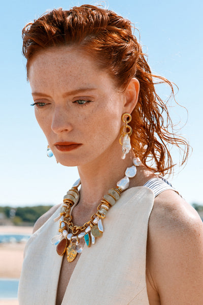 Thumbnail of model wearing the Seascape Necklace. Take style cues from beyond the sea in our multi-strand gold chain statement necklace. This mixed media treasure has it all; with beads of chunky freshwater pearl, bottle green glass, and semiprecious aventurine and turquoise charms.