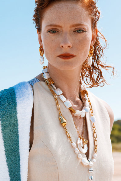 "Thumbnail of model wearing the Garda Pearl Collar. Being square will be anything but basic when you don our unique freshwater cultured ""square"" pearl collar necklace. With gold-plated fluted accent beads and hook closure."