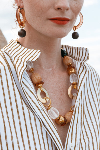 Thumbnail of model wearing the Como Necklace. Spice up your spring wardrobe in this flattering, warm-toned single-strand necklace. Gold-plated rings meld with an assortment of black, clear, and dune-colored beads and links for a piece you'll be excited to throw on with everything.