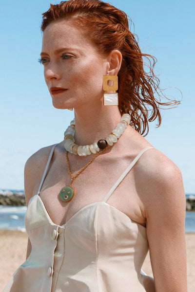 Thumbnail of model wearing the Fortune Necklace In Wave. Ready for a sea change? It's our latest iteration of the ever-popular Fortune Necklace, in gold vermeil with a substantial green aventurine pendant. Inset with a constellation of mother-of-pearl, pink tourmaline, and faceted citrine stones.