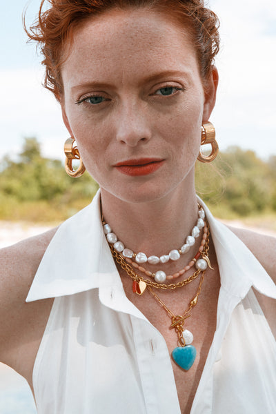 Thumbnail of model wearing the Cornetto Necklace. Artfully mix your materials in our multi-strand freshwater pearl, coral, and gold-plated chain necklace that looks like you've flawlessly layered three independent accessories (we won't tell!). With dainty gold-plated cornicello and heart charms.