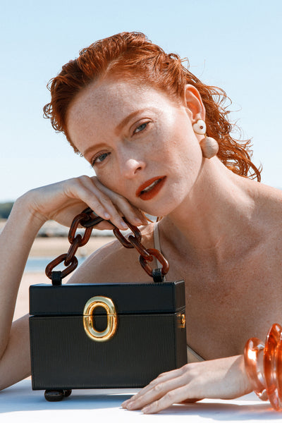Thumbnail of model holding the Cinema Box Bag In Onyx. Combining the nostalgic silhouette of...