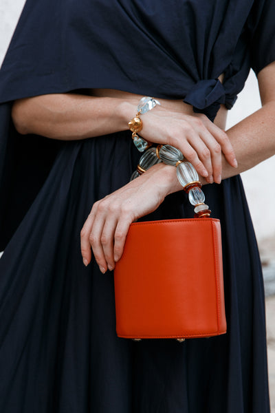 Thumbnail of model carrying the Florent Bag In Persimmon. Buon Giorno! Wake up your wardrobe...