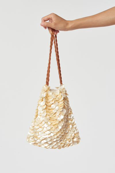 Thumbnail of model holding Gala Wristlet In Beachcomber. Possibly our most popular new clutch style (especially amongst all the editors at Fashion Week), the brand new Beachcomber drawstring purse is the perfect honeymoon or vacation weekend wristlet. We love the layered pearl motif - it feels like a treasure from the sea.