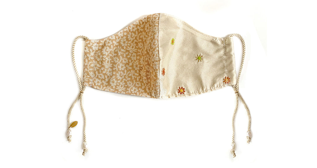 Face Mask In Cloud. Face mask featuring neutral floral and embroidered flower motif silk fab...
