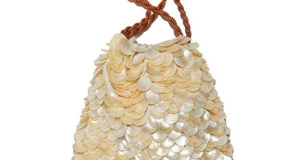 Close-up of Gala Wristlet In Beachcomber. Possibly our most popular new clutch style (especially amongst all the editors at Fashion Week), the brand new Beachcomber drawstring purse is the perfect honeymoon or vacation weekend wristlet. We love the layered pearl motif - it feels like a treasure from the sea.