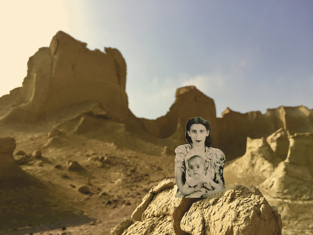 An  image of an iranian mother and child, the artist's family, before rocks in a desert landscape.