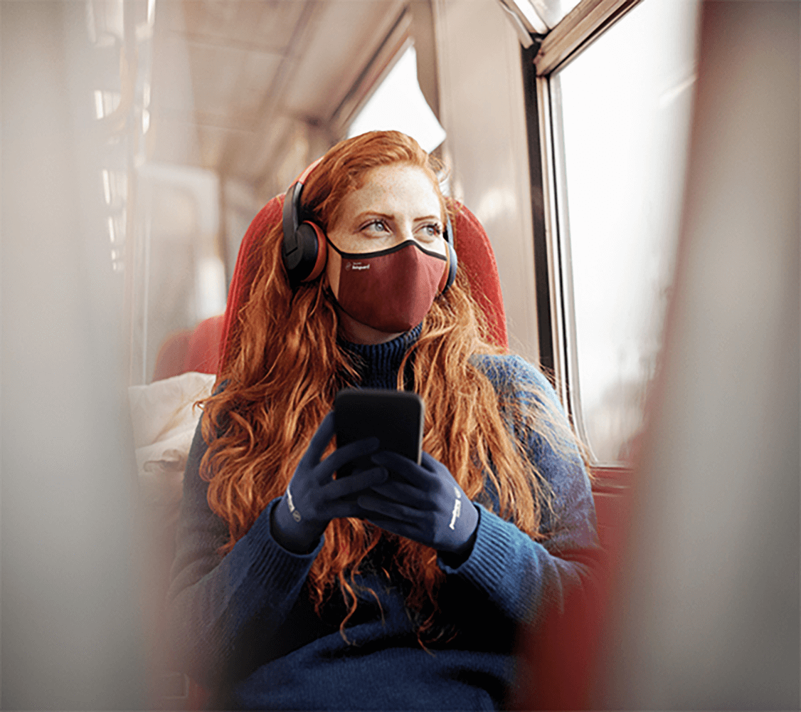 image of a woman wearing a cosmic red pro mask from Livinguard in a train