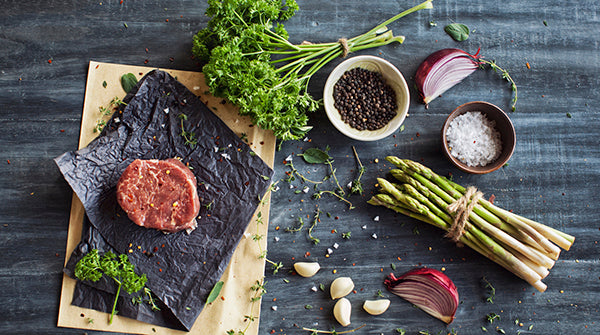 Raw tenderloin steak with seasoning, garlic, and asparagus