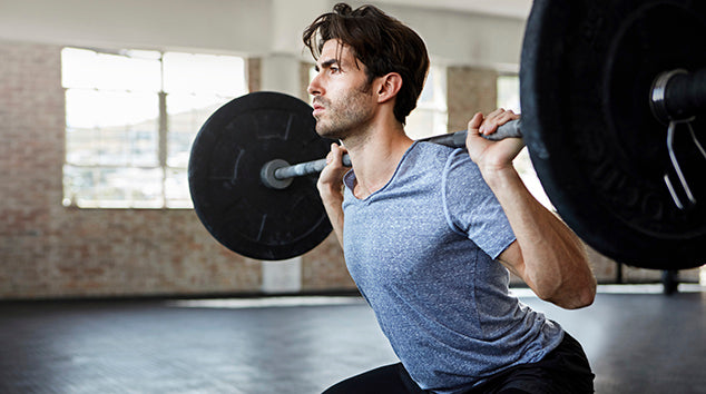 Shot of a young man working out with weights in the gym