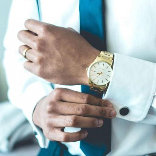 man wearing a yellow gold watch and wedding band