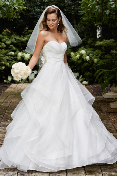 Simple and stunning, this tulle ballgown features a silky taffeta ruched bodice and waistband, sweetheart neckline, and multi-layer skirt with horsehair hem. Two silky taffeta and tulle flowers with crystal centers accent the back bodice perfectly. Chapel train.
