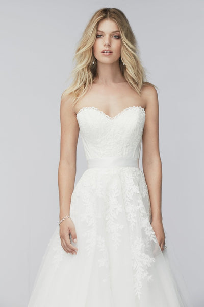 Romantic, elegant, feminine—this ivory skirt with a chapel train is one of the most versatile in our wedding collection. With its layers of poly-lined tulle adorned with Adette lace, it pairs beautifully with everything from vintage-lace corsets to fitted organza bustiers. (The wide range of options make it one of our bridal stylists' favorites.) A double-faced satin ribbon cinched at the waist adds feminine appeal. For the bride who wants to truly customize her wedding day look, it's a lovely option to fi