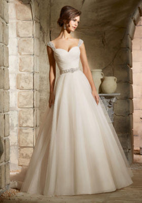 Perfect for a princess bridal look, this simple Tulle Bridal Ball Dress features an asymmetrically draped sweetheart bodice and full A-line skirt. Glimmering detachable cap sleeves and a beaded waistband add the perfect amount of sparkle. Covered button detail accents the back. Chantilly