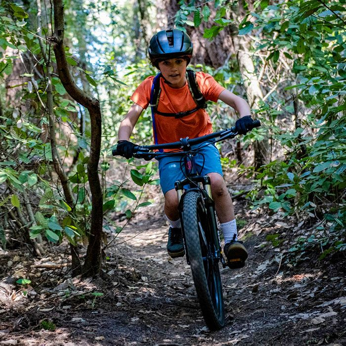 boy riding mountain bike down a slope wearing the bell sidetrack II helmet, front view