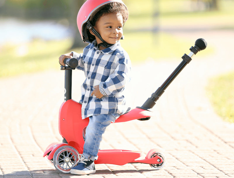 boy riding Micro Mini2go 3 wheel kick scooter in red with seat and push rod