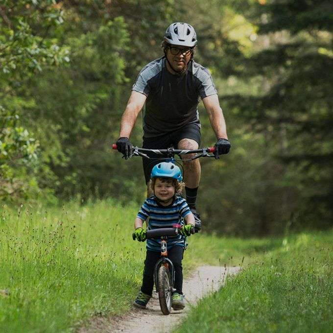 boy wearing giro scamp helmet for kids, cycling on a bicycle with father