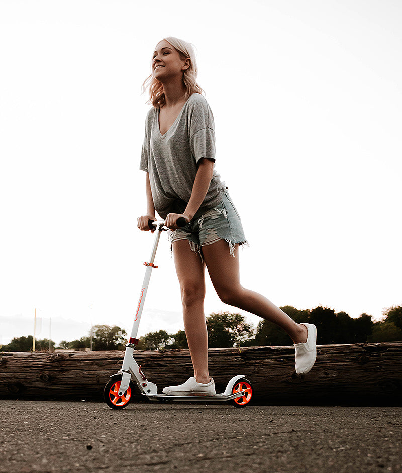young woman riding Glideco CityZipper145 kick scooter in White/Pink