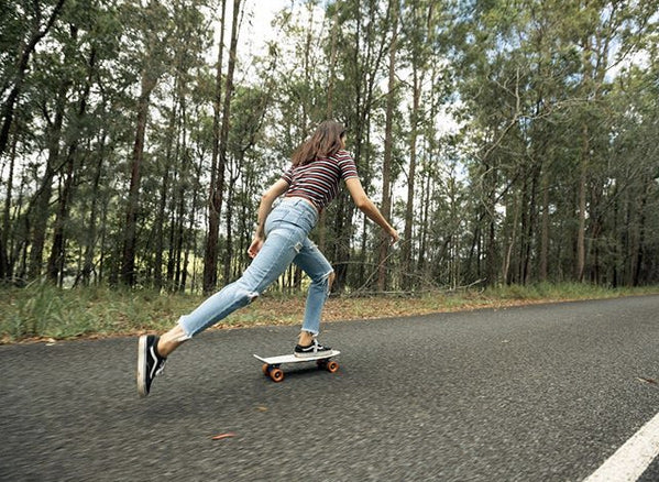 girl riding penny 22 inch skateboard on country road