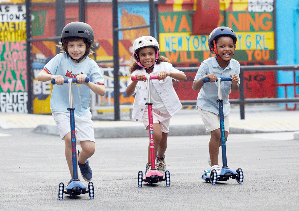 kids riding the maxi micro deluxe LED three wheel kick scooter