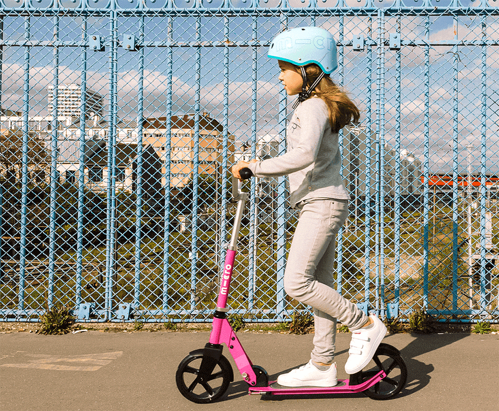 girl riding micro cruiser kick scooter in pink