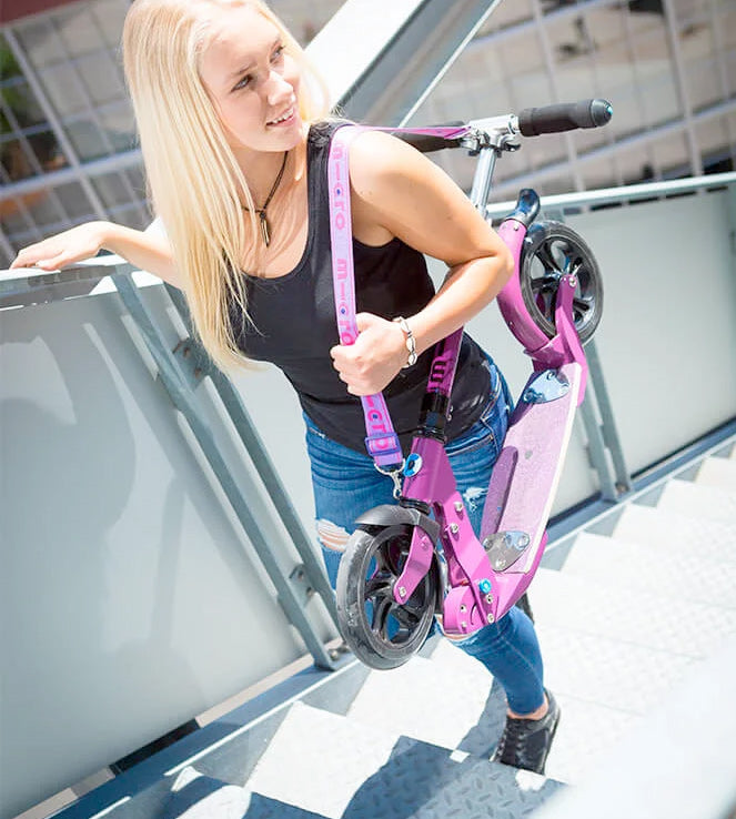 girl carrying kick scooter on shoulder using micro strap
