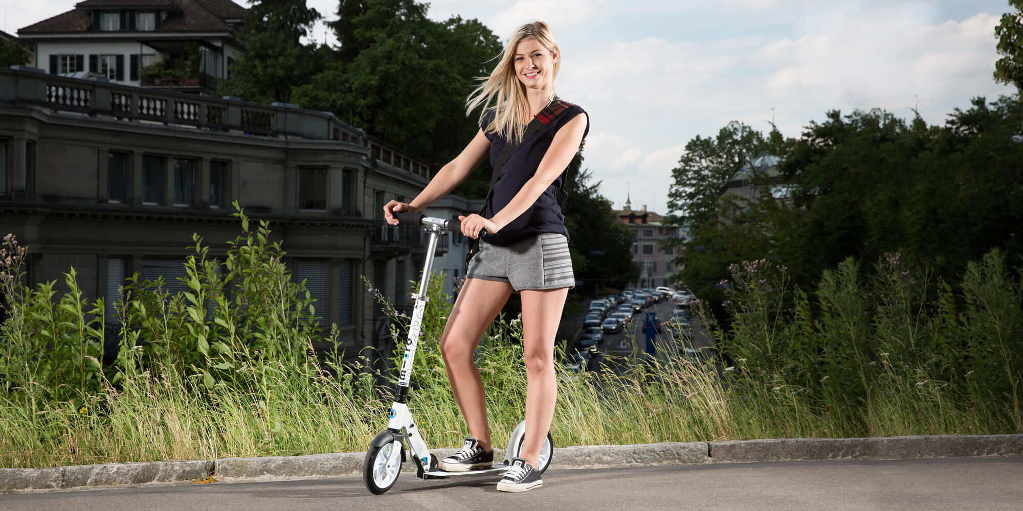 Micro white kick scooter with adult female rider