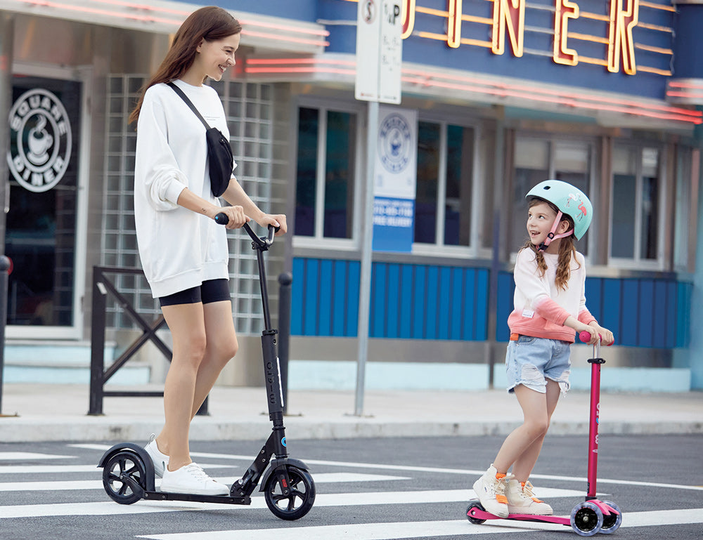 young mother accompanying a young girl riding the maxi micro deluxe LED kick scooter