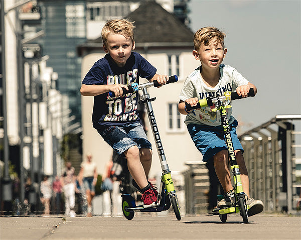 Young boys riding 2 wheel kick scooters
