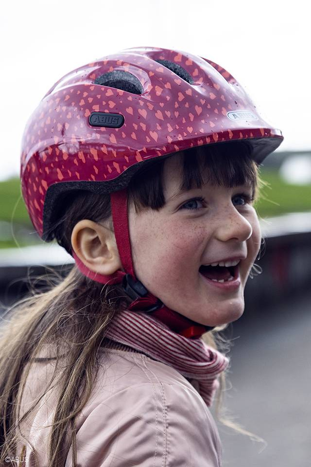young girl wearing abus smiley 2.0 bicycle helmet in pink