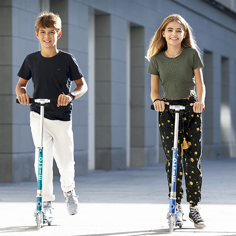 Kids riding Micro Sprite LED two wheel kick scooters