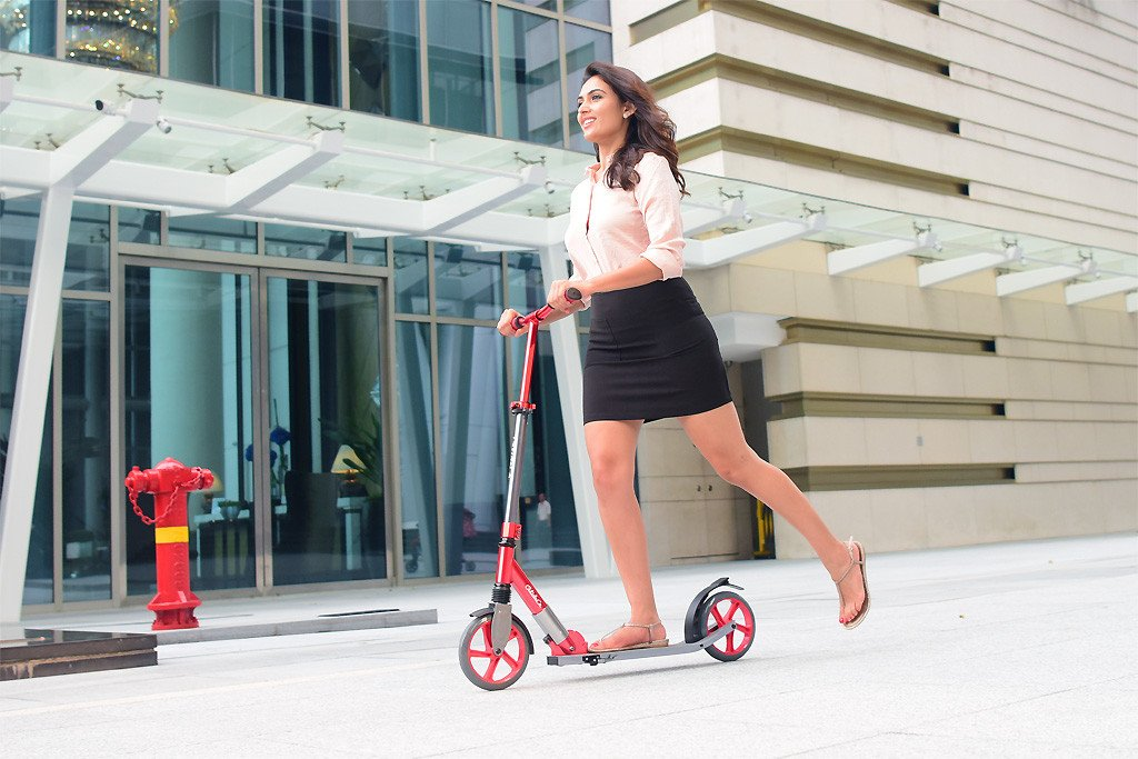 young woman riding Glideco Cruiser200 kick scooter in red